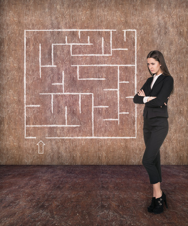 way of thinking: Young businesswoman looking at the labyrinth and thinking about right way on light red brick background