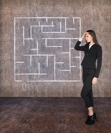 Young businesswoman looking at the labyrinth and thinking about right way on grey brick background photo