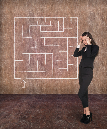 way of thinking: Young businesswoman looking at the labyrinth and thinking about right way on light red background Stock Photo