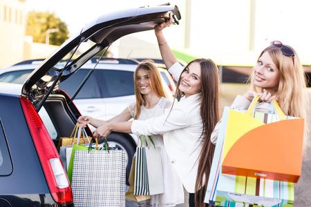 Gruppo di ragazze dopo l'acquisto di caricare le borse della spesa in un bagagliaio di un'auto