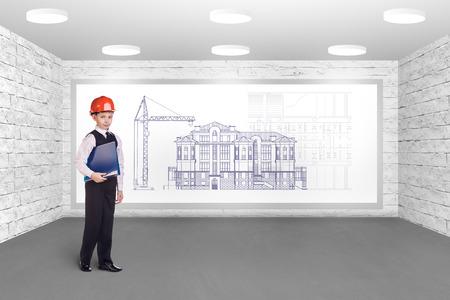 Little builder in helmet thinking in front of plan photo