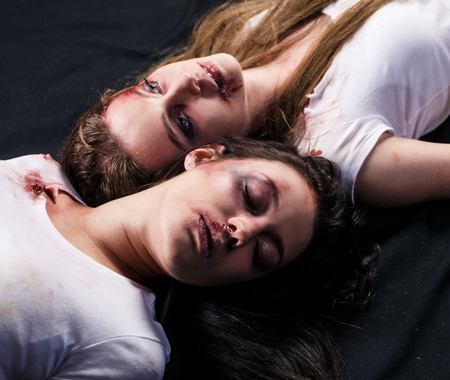 beaten up: Two young beaten women with cuts and bruises lie down on the floor on black background Stock Photo