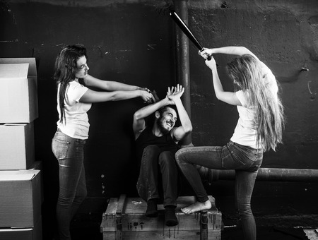 beard woman: Two young women beaten man sitting on the box in basement on black-and-white background