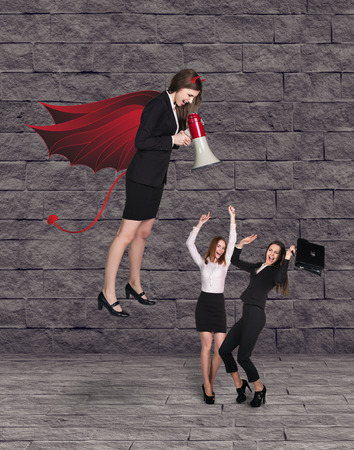 businesslady: Devil businesslady with a megaphone screemingat another businessladies Stock Photo