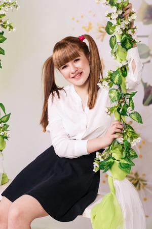 elegant girl: Young girl in school cloths sitting in swinging chair