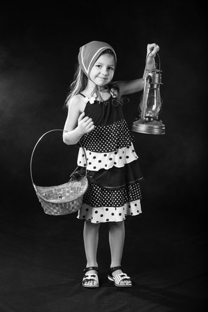 oillamp: The black-and-white portrait of beautiful little girl in dress and red scarf standing with basket and oil-lamp
