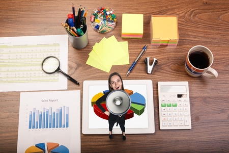 Woman with megaphone on office table. Desk office financial accounting graphs analysis photo