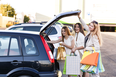Group of girls after shopping loading a shopping bags in a car trunk