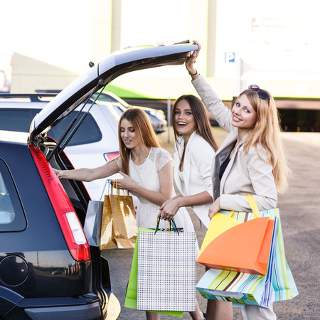 Group of girls after shopping loading a shopping bags in a car trunk photo