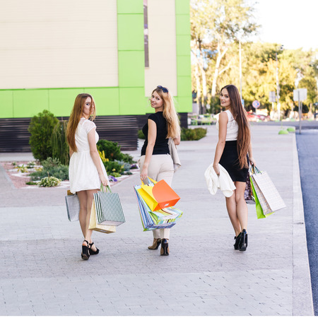 turn away: Girls holding shopping bags and walk around the shops. Smiling girlfriends having fun together