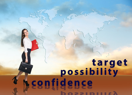 work worker workforce world: Image of confident businesswoman with briefcase walking up to target.