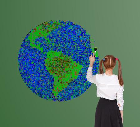 Schoolgirl drawning globe on the blackboard photo