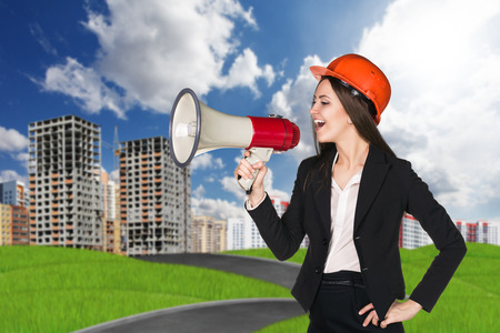 grass plot: Woman in hardhat with megaphone making announce