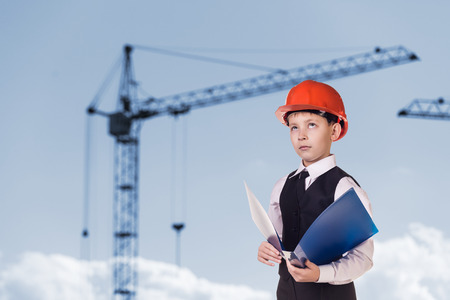 fun at work: Child in helmet on the building site Business