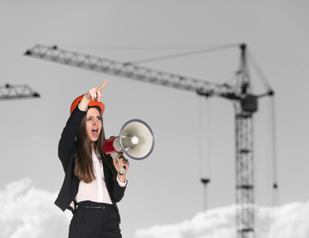 Young woman builder in hardhat screaming in megaphone photo