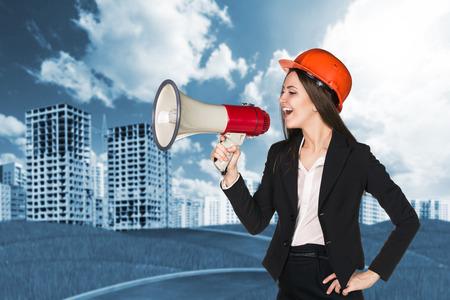 anunciar: Mujer en sombrero duro con el meg�fono haciendo anunciar