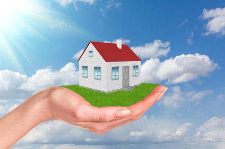 sfondo nuvole: Mano che tiene casa sul prato verde con alberi, il vento. Sfondo Nuvole e cielo blu