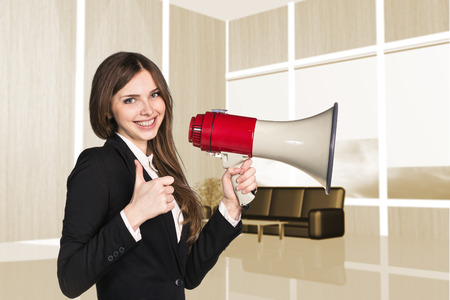 business attire teacher: Businesswoman with megaphone in the office. Thumb up