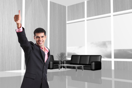 bussinessman: Happy bussinessman giving thumbs up in the modern office Stock Photo