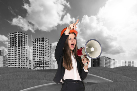 grass plot: Angry businesswoman in hardhat screaming in megaphone Stock Photo