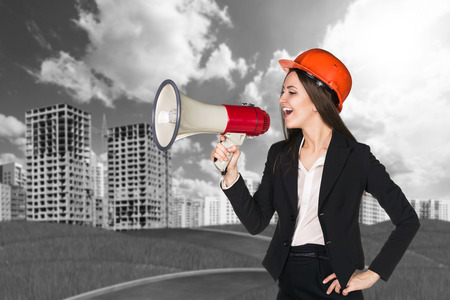 announce: Woman in hardhat with megaphone making announce
