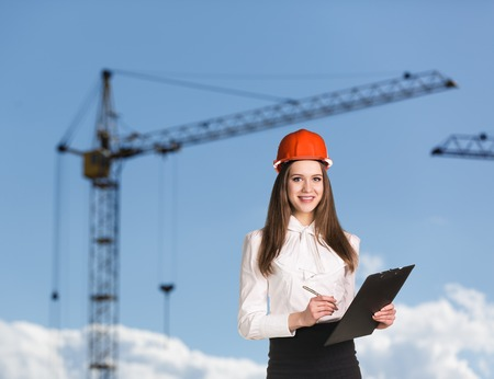 Smiling woman in hardhat on the building side photo