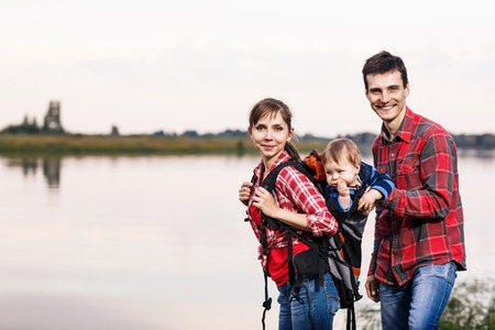 Happy family outdoors. Baby boy in backpack carrier on walking tour. photo