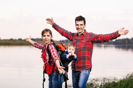 Happy family outdoors with hands outstretched. Baby boy in backpack carrier on walking tour. photo