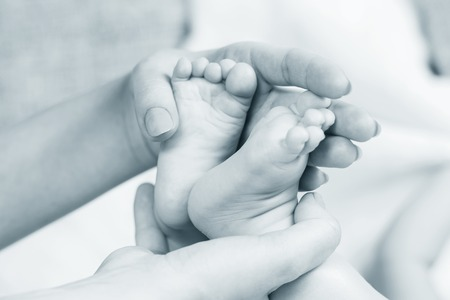firstborn: baby legs in mother hands