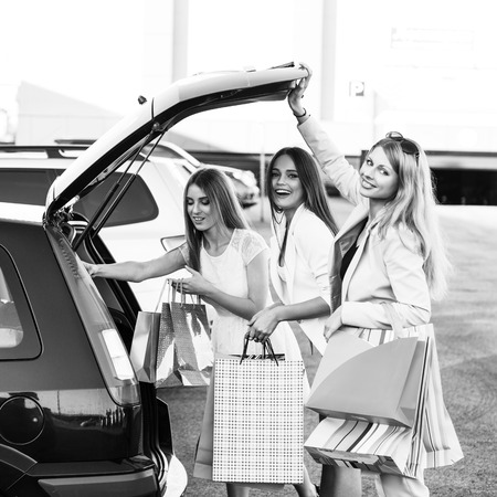 car trunk: Group of girls after shopping loading a shopping bags in a car trunk