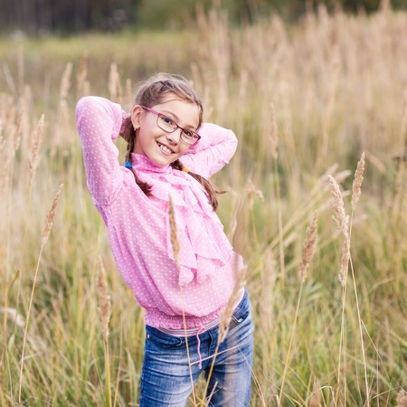 Adorable teenage girl in glasses at autumn field.