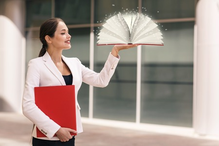 Businesswoman with a book and a folder Stock Photo