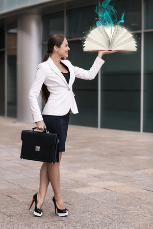 Businesswoman with a book and a briefcase Stock Photo