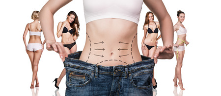 Woman shows her weight loss. Isolated on white background Stock Photo