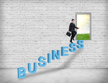 rural development: A man with a briefcase is climbing on business text