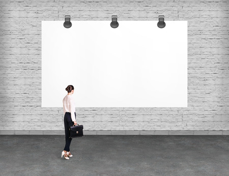 advertise: Elegant business woman standing and looking at blank white billboard. Copy-space for advertise.