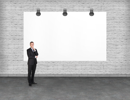 advertise: Elegant businessman standing near blank white billboard. Copy-space for advertise.