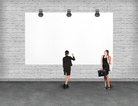 advertise: Elegant business women standing and looking at blank white billboard. Copy-space for advertise.