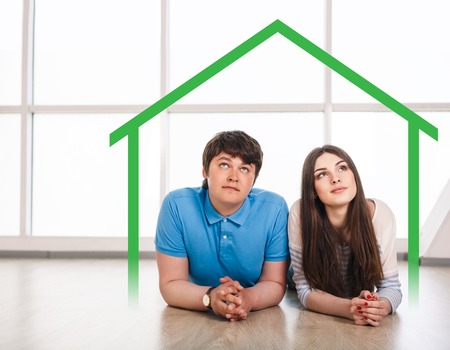 real estate planning: Happy young couple lying on the floor at home, dreaming