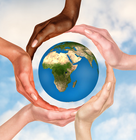 Beautiful conceptual symbol of the Earth globe with multiracial human hands around it. Unity and world peace concept. Elements of this image furnished by NASA Stockfoto