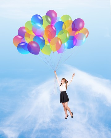 baloons: Happy girl with baloons flying on sky background