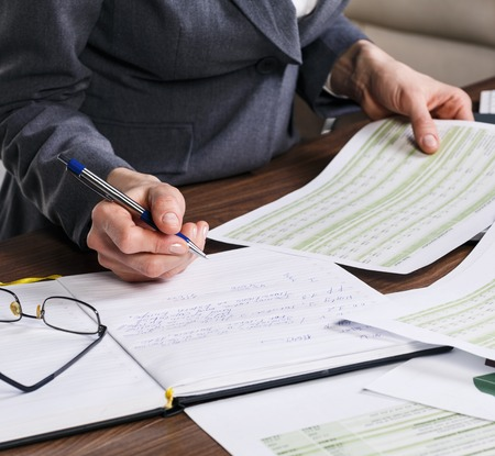 working papers: Close up of a female hand calculating, on the office desk. Stock Photo