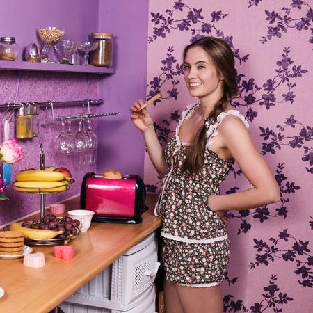 comiendo pan: Atractiva ama de casa que come la tostada en la cocina