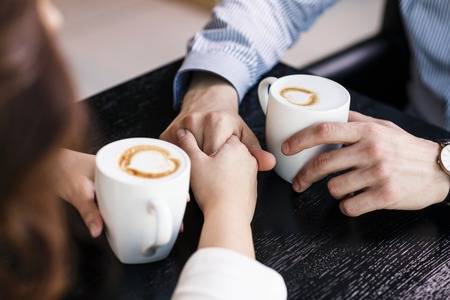 Hands on the table  holding cups of coffee Imagens