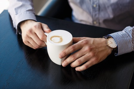 man relax: Businessman taking a break at the office as he enjoys a cup of hot aromatic coffee, close up view of his hands