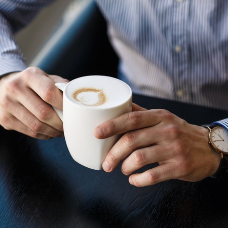 man drinking coffee: Businessman taking a break at the office as he enjoys a cup of hot aromatic coffee, close up view of his hands