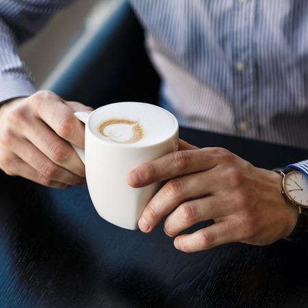 hombre tomando cafe: Hombre de negocios tomando un descanso en la oficina mientras se disfruta de una taza de arom�tico caf� caliente, vista de cerca de las manos Foto de archivo