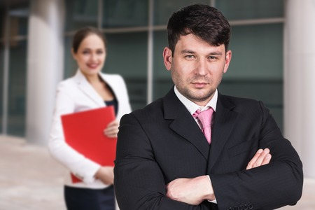 Handsome businessman and businesswoman exploring documents in a red folder