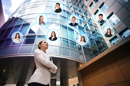 team worker: Beautiful young business woman. Modern building behind her