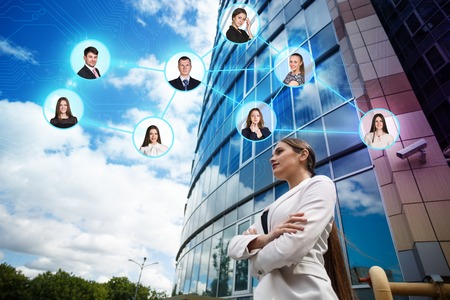 casual business: Beautiful young business woman. Modern building behind her